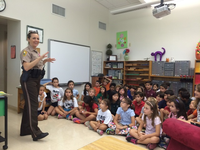 An officer talking to a class of students during red ribbon week